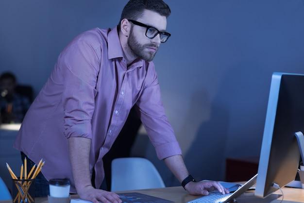 Чувствую себя комфортно. серьезный умный сконцентрированный мужчина стоит за столом и смотрит в экран компьютера, ожидая, что что-то произойдет