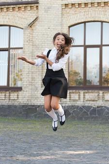 편안한 느낌. 소녀는 세련된 옷을 입는다. 흰 셔츠와 검은 드레스. 학교 방문을 위한 정장. 데일리룩. 사랑스러운 여학생. 딱 어울리는 옷. 아동복. 학교 패션.