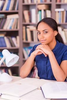 彼女の最終試験に自信を持っています。手に顔を立てて、図書館の机に座ってカメラを見ている自信を持って若い黒人女性