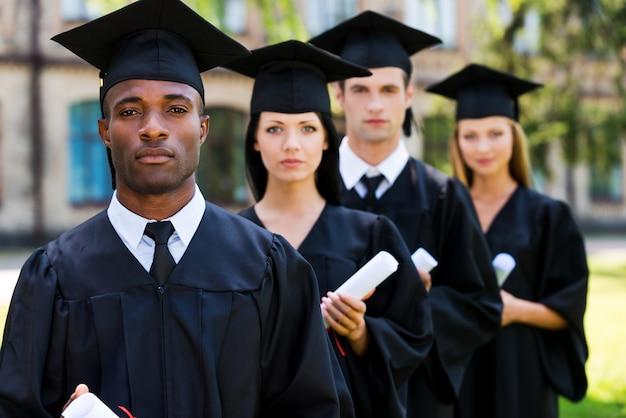 彼らの将来に自信を持っています。 4人の大学卒業生が並んでカメラを見ている