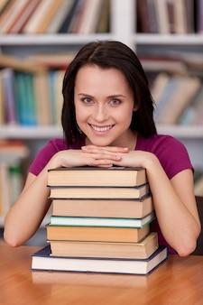 彼女の最終試験の前に自信を持っています。本を持って図書館に立って笑っている元気な若い女子学生