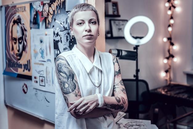 Чувствую себя уверенно. необычайно привлекательная девушка с короткими волосами в рубашке без рукавов и своими необычными татуировками.