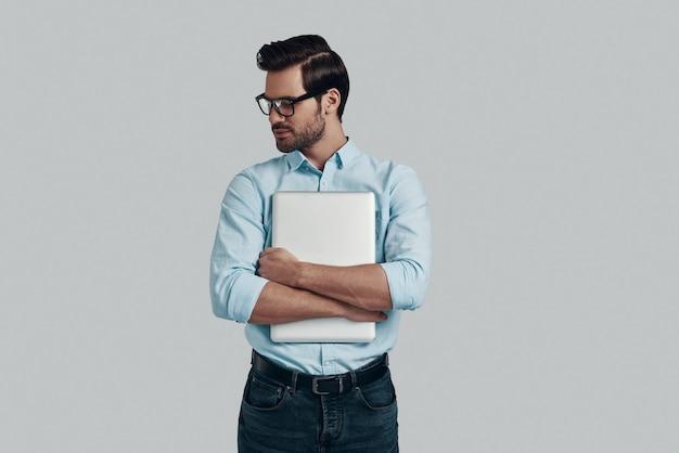 自信を持っています。ラップトップを携帯し、灰色の背景に立って笑っているハンサムな若い男