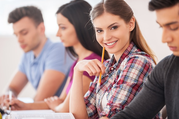 Feeling confident in her knowledge. four cheerful students studying together while sitting at the desk while beautiful woman holding pencil and smiling at camera