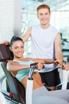 그녀의 강사에 대한 자신감이 느껴집니다. 그녀의 근처에 서 있는 잘생긴 남성 강사 동안 체육관에서 운동하는 아름 다운 젊은 여자