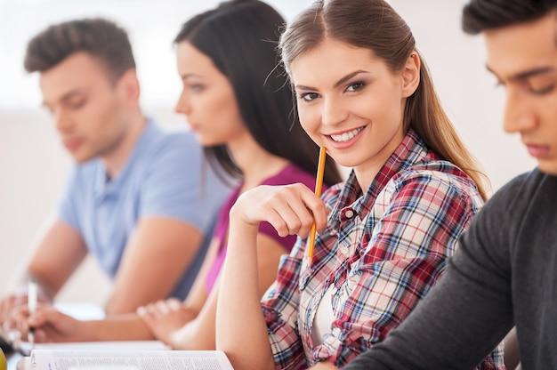 彼女の知識に自信を持っている。鉛筆を持ってカメラに微笑んでいる美しい女性が机に座って一緒に勉強している4人の陽気な学生