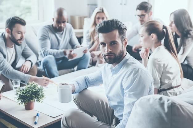내 팀에 대한 자신감을 느낀다. 젊은 남자가 커피 컵을 들고 어깨 너머로 바라보는 동안 사무실 책상에 함께 앉아 무언가를 토론하는 자신감 있는 사업가 그룹