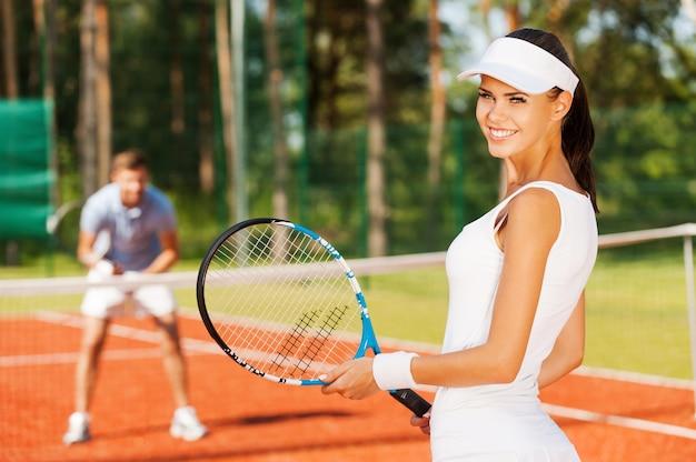 우승에 대한 자신감이 생깁니다. 테니스 라켓을 들고 어깨 너머로 웃고 있는 아름다운 젊은 여성, 스포츠 의류를 입은 남자가 뒤에 서 있는 동안