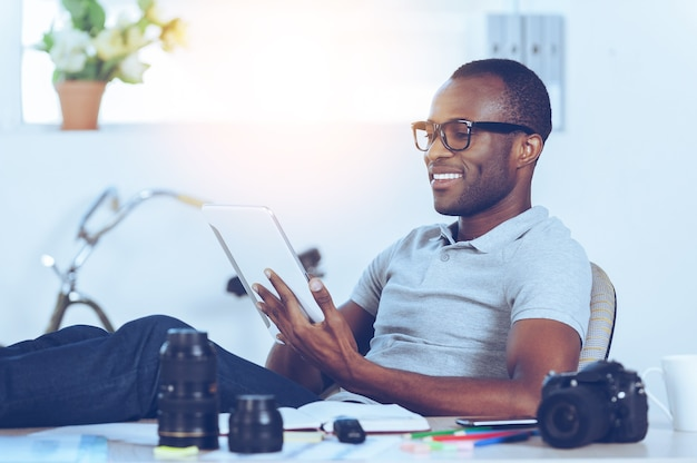 Feeling confident and relaxed. handsome young african man in casual wear sitting at his working place and working on digital tablet