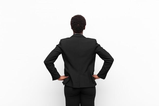 Чувство смущения или полноты или сомнения и вопросы, интересно, с руками на бедрах, вид сзади