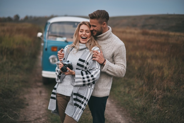 Feeling cozy together. beautiful young couple embracing and smiling while standing outdoors