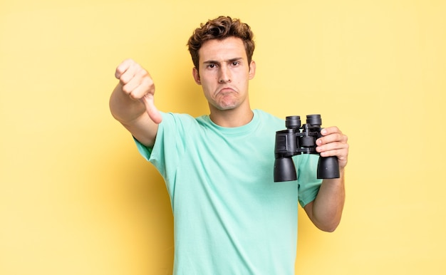 Feeling cross, angry, annoyed, disappointed or displeased, showing thumbs down with a serious look. binoculars concept