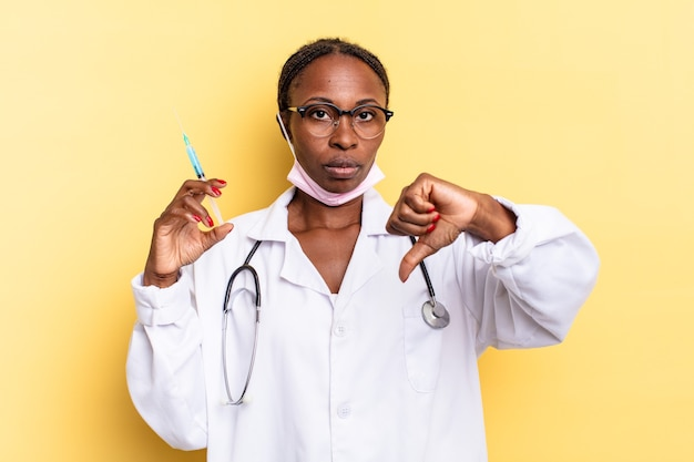 Feeling cross, angry, annoyed, disappointed or displeased, showing thumbs down with a serious look. physician and syringe concept