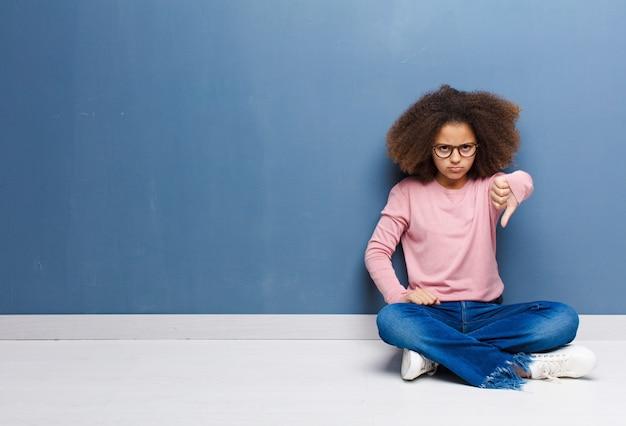 Чувство злости, злости, раздражения, разочарования или недовольства, показывающее палец вниз с серьезным взглядом
