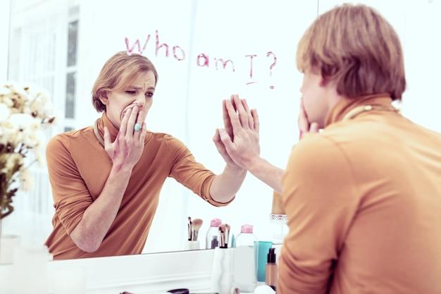 くさくさ。ストレスの多いジェンダークィアの少年が鏡に逆らって滞在している間、彼の精神に混乱している