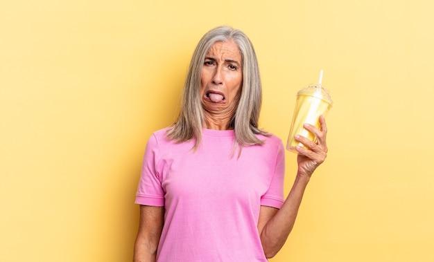 Чувство отвращения и раздражения, высунутый язык, неприязнь к чему-то мерзкому и противному и держит в руках молочный коктейль.