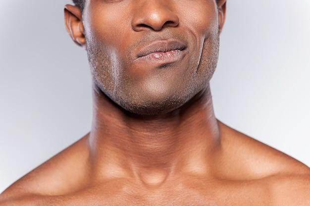 의심을 느낀다. 회색 배경에 서 있는 동안 찡그린 젊은 아프리카 남자의 자른 이미지