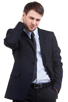 疑問を感じています。白で孤立して立っている間彼の首に触れて見下ろしている正装で欲求不満の若い男