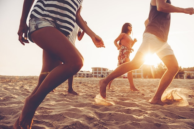 Feeling energy inside. group of young cheerful people running along the beach and looking happy