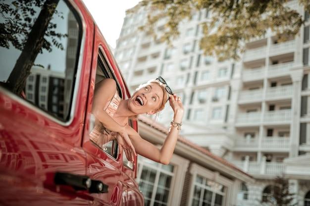 흥분 느낌. 그녀의 선글라스를 벗고 차 창 밖으로 기대어 쾌활 한 놀란된 여자.