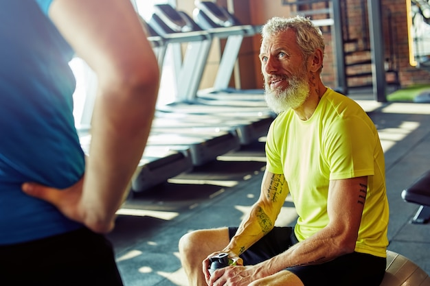 Feeling exhausted caucasian middle aged man in sportswear holding bottle of water and talking with