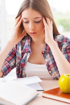 Чувствовать себя опустошенным. разочарованная девочка-подросток держит голову руками, сидя за столом с лежащими на нем книгами