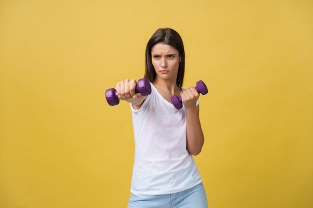 疲れた感じ。黄色の背景に孤立して立っている間、ダンベルと真剣な表情で運動している白いシャツの欲求不満の若い女性。