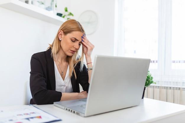 疲れた感じ。職場に座って眼鏡を手に持って疲れ果てているように見える欲求不満の若い女性