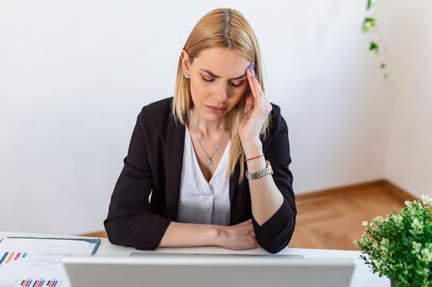지친 느낌. 그녀의 작업 장소에 앉아있는 동안 지쳐 보이는 좌절된 젊은 여자