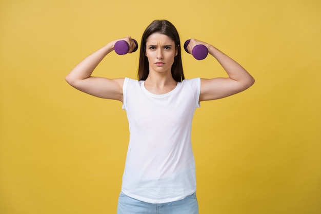Feeling exhausted. frustrated young woman in white shirt exercising with dumbbells and serious look while standing isolated on yellow background.