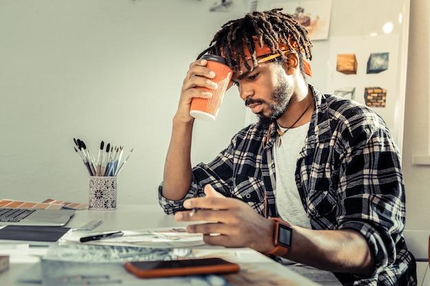 疲れた感じ。疲れを感じながら赤い一杯のコーヒーを保持している若い創造的なインテリアアーティスト