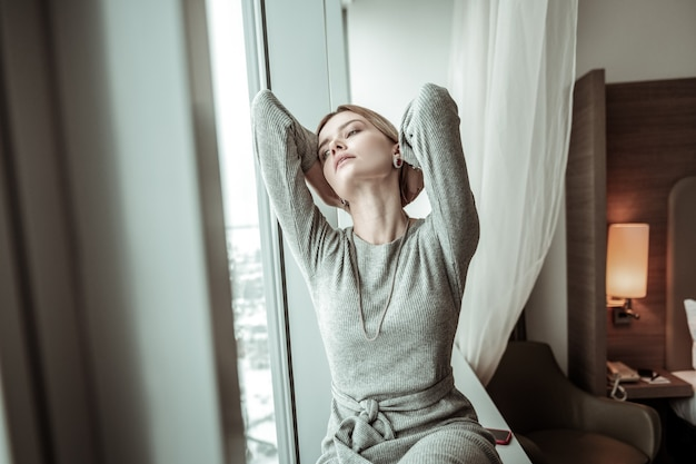 Feeling exhausted. young woman looking into window while feeling exhausted after hard day in the office