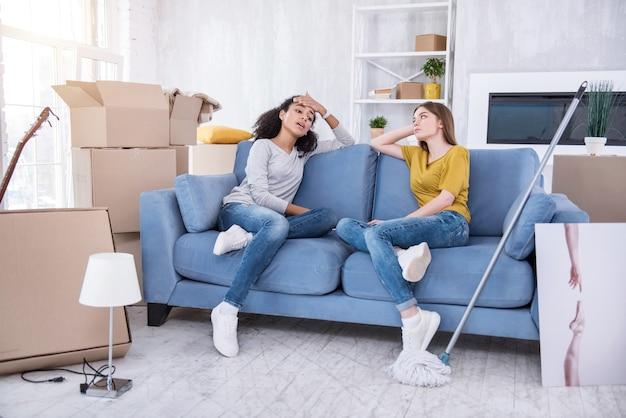 Чувство усталости. очаровательные молодые девушки сидят на диване и вытирают пот со лба, уставшие после уборки в новой квартире