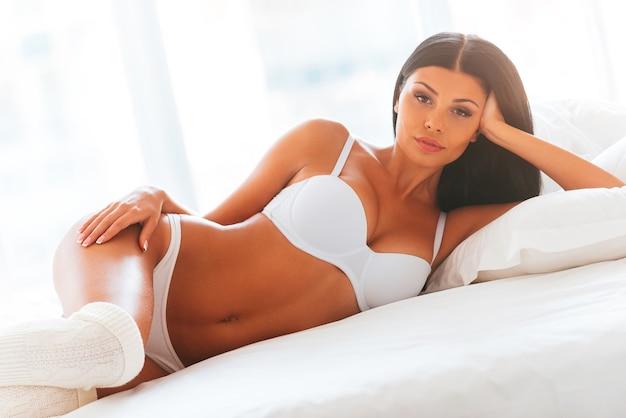 Ощущение кокетливости. красивая молодая женщина в нижнем белье и белых носках, лежа в постели и глядя в камеру