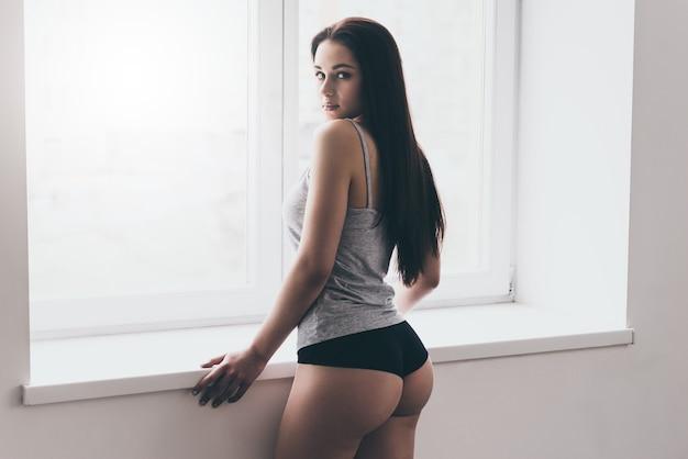 軽薄な感じ。窓枠に寄りかかって肩越しに見ているパンティーとタンクトップの美しい若い女性の背面図