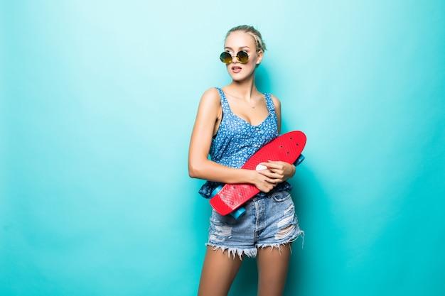 自由で幸せな気分。青い背景に立っている間笑顔とスケートボードを運ぶサングラスの魅力的な若い女性