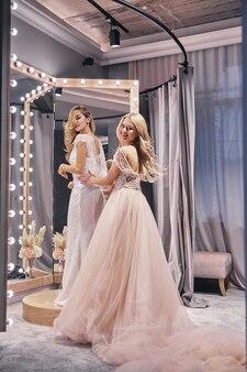 자유롭고 행복한 느낌. 피팅 룸에 서 있는 동안 그녀의 여자 친구에 드레스를 조정 하는 젊은 아름 다운 여자의 전체 길이