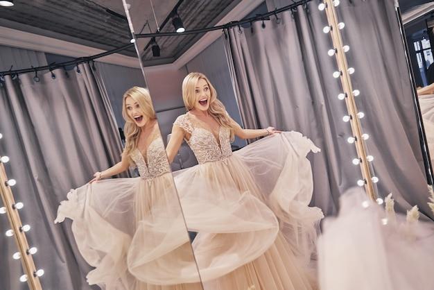 자유롭고 행복한 느낌. 웨딩 드레스를 입고 신부 가게에 서 있는 동안 입을 벌리고 있는 아름다운 젊은 여성의 반영