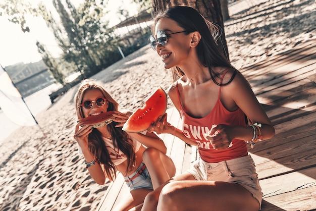 Чувствуя себя свободным и счастливым. вид сверху двух привлекательных молодых женщин, улыбающихся и едящих арбуз, сидя на пляже