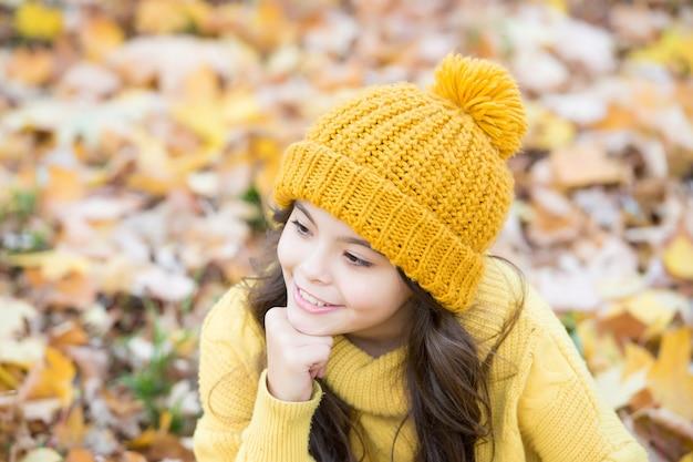 자유롭고 편안한 느낌. 가을 니트 패션. 영감을위한 낭만적 인 계절. 행복한 어린 시절. 소녀는 공원에서 휴식을 취하십시오. 가을 시즌의 아름다움. 숲에서 하루를 즐길 수 있습니다. 모자에 웃는 아이 야외 휴식.