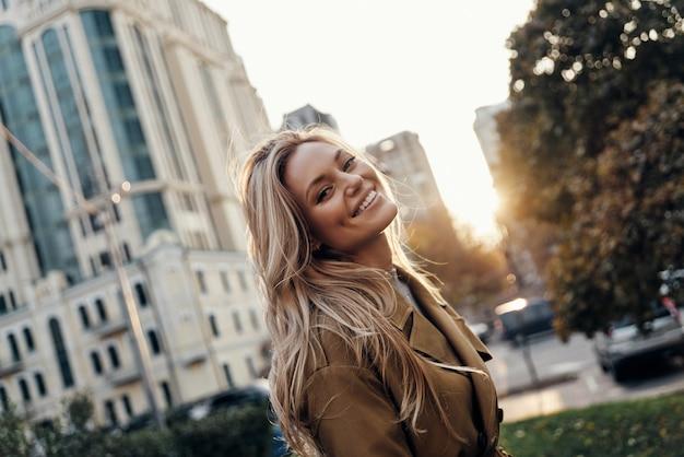 자신이 될 수 있는 자유를 느낍니다. 카메라를 보고 야외에 서서 웃고 있는 매력적인 젊은 여성