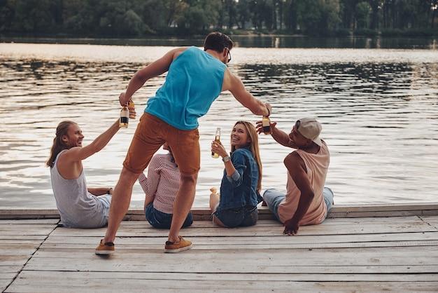 何でも気軽に。桟橋に座って笑顔でビールを飲みながらカジュアルな服装で幸せな若者のグループ