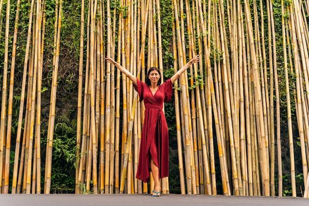 自由を感じる。竹林の近くに立って腕を上げ、笑顔を見せてくれる魅力的な若い美女