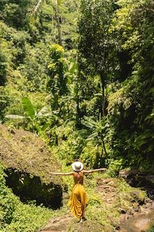 自由を感じる。彼女の旅行ブログを撮影しながらジャングルに顔を向けて立っているスリムな女性