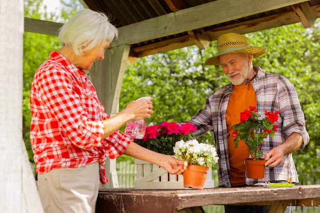 기분이 좋다. 함께 꽃에 물을 주면서 기분이 좋은 나이 든 잘 생긴 남편과 아내