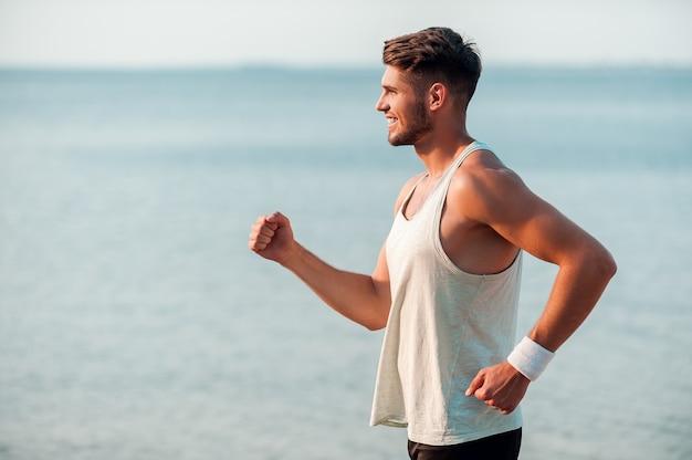 気分が良く、健康を維持します。川岸に沿って走っている笑顔の若い筋肉の男の側面図