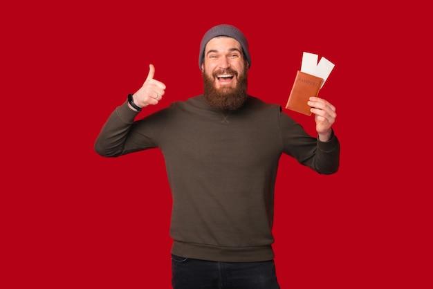 기분이 좋은 수염 난 남자가 엄지손가락을 보여주면서 티켓과 함께 여권을 들고 있습니다.