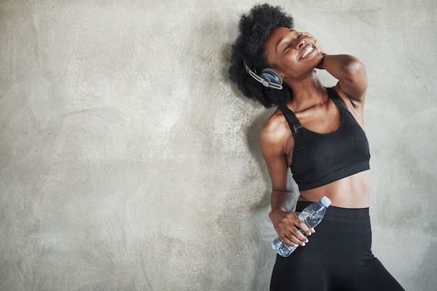 Feeling good. portrait of african american girl in fitness clothes having a break after workout