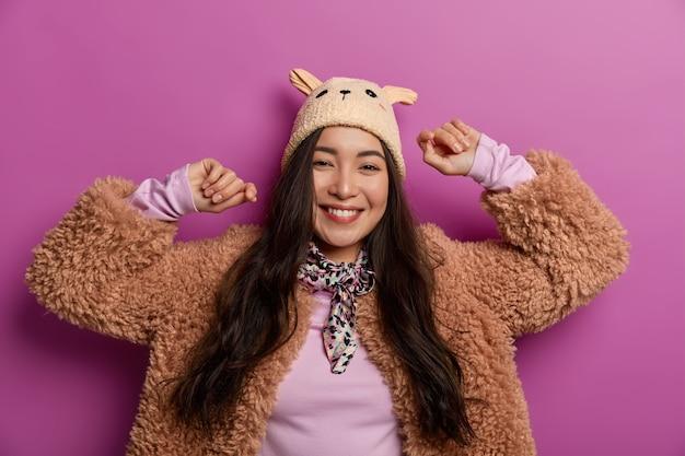Sentirsi bene e rilassati. splendida signora asiatica ottimista indossa buffo cappello e cappotto, si muove spensierata contro lo spazio lilla, si diverte e balla