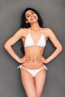 위대하고 멋지게 보입니다. 회색 배경에 서 있는 동안 엉덩이에 손을 잡고 웃고 있는 흰색 비키니를 입은 아름다운 젊은 혼혈 여성